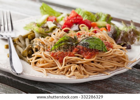 whole wheat spaghetti topped with organic homemade marinara sauce served with green beans and an Italian side salad on an old weathered barn wood table macro shot