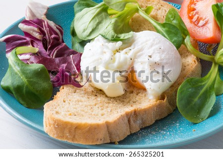 Whole wheat toasted bread with poached egg, runny egg yolk and fresh green salad leaves on blue plate. Close up healthy food image - stock photo