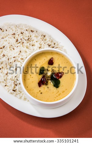 Whole Yellow Lentil with Rice, dal tadka and jeera rice, Indian Dish, cooked rice and cooked Arhar or Toor dal (Pigeon Pea), served in a white plate,cropped view on orange background, top view - stock photo
