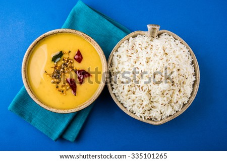 Whole Yellow Lentil with Rice, dal tadka and jeera rice, Indian Dish, cooked rice and cooked Arhar or Toor dal (Pigeon Pea), served in ceramic bowl, top view, isolated on blue background - stock photo