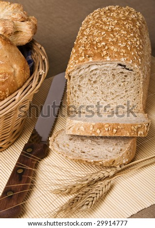 Wholegrain bread loaf with oats flakes on it. Focus on bread. - stock photo