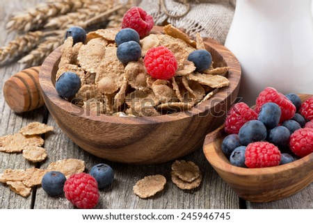 wholegrain flakes with fresh berries and jug of milk on wooden table, close-up - stock photo