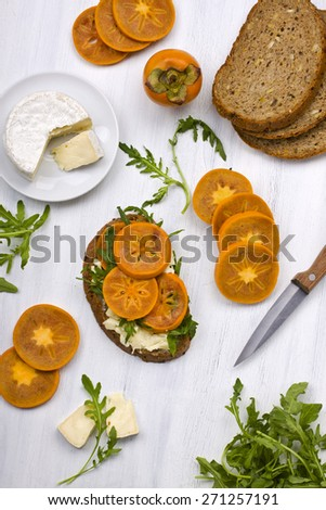 Wholegrain sandwich with soft cheese and fresh ripe persimmon - stock photo