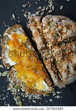 Wholemeal bread, one slice spread with butter and orange marmalade - stock photo