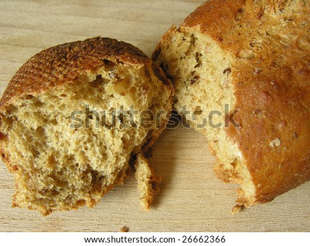 Wholemeal bread roll with seeds and grains, broken into two pieces, showing both crust and inside of bread, on a wooden board. - stock photo