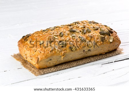 Wholemeal bun on white wooden background, closeup. - stock photo