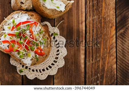 Wholemeal sandwiches with soft cheese, fresh pepper and radish sprouts on the wooden table
