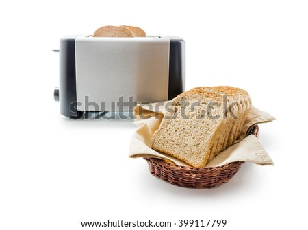Wholemeal toast bread slices placed on a cotton cloth napkin in a wicker basket close up arranged with electric toaster isolated on white background. - stock photo