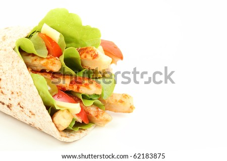 Wholemeal tortilla wrap with chicken stripes and lettuce - stock photo