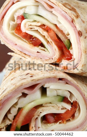 Wholemeal tortillas with ham, cheese, tomatoes, cucumber and cabbage - stock photo