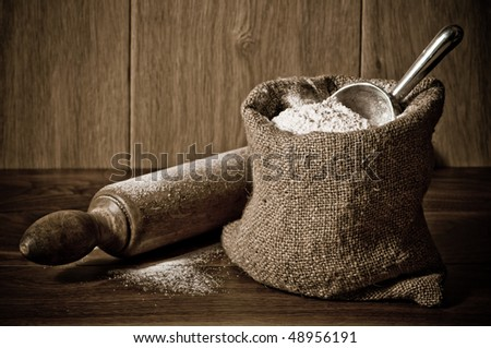 Wholemeal wheat flour in burlap sack with antique rolling pin - stock photo