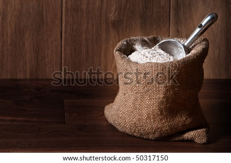 Wholemeal wheat flour in burlap sack with scoop, copy space included - stock photo