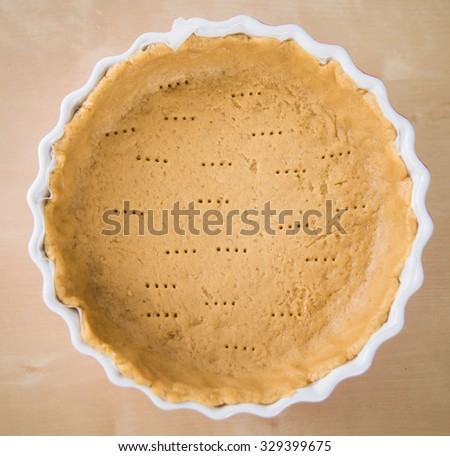 Wholemeal whole wheat pie crust in ceramic oven dish