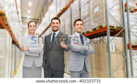 wholesale, logistic, business, export and people concept - happy man in suit and tie showing thumbs up gesture over warehouse background - stock photo