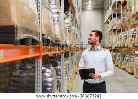 wholesale, logistic, business, export and people concept - man or manager with clipboard checking goods at warehouse - stock photo