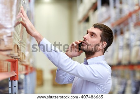 wholesale, logistic, business, export and people concept - serious businessman calling on smartphone at warehouse - stock photo