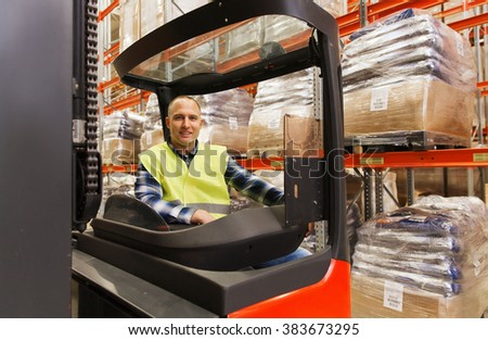 wholesale, logistic, loading, shipment and people concept - smiling man or loader operating forklift loader at warehouse - stock photo