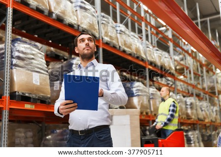 wholesale, logistic, people and export concept - businessman with clipboards at warehouse