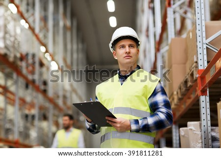 wholesale, logistic, people and export concept - man with clipboard in reflective safety vest at warehouse - stock photo
