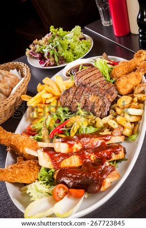 Wholesome platter of mixed meats including grilled steak, crispy crumbed chicken and beef on a bed of fresh leafy green mixed salad served with French fries and chutney or BBQ sauce in a dish - stock photo