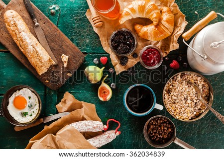 Wholesome rustic breakfast with cereal, fried egg, bread, jams, sausage, milk in a can and coffee spread out on a green wooden background, overhead view - stock photo