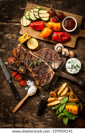 Wholesome spread with t-bone or porterhouse steak served with an assortment of healthy roasted vegetables and savory dips on a rustic wooden table in a country kitchen - stock photo