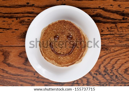 Wholesome whole wheat pancakes with a caramel sauce good morning smile - stock photo