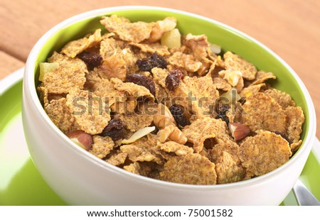 Wholewheat cereal with dried fruit, raisin, walnut and almond in bowl (Selective Focus, Focus in the middle of the bowl) - stock photo