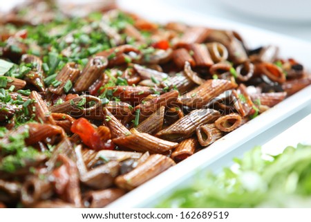 Wholewheat Italian pasta served with herbs and tomato in a flat open dish on a buffet table for healthy vegetarian cuisine, close up view with shallow dof - stock photo