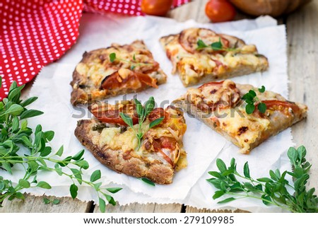 Wholewheat wholemeal pizza with tomatoes, cheese and herbs. Selective focus - stock photo