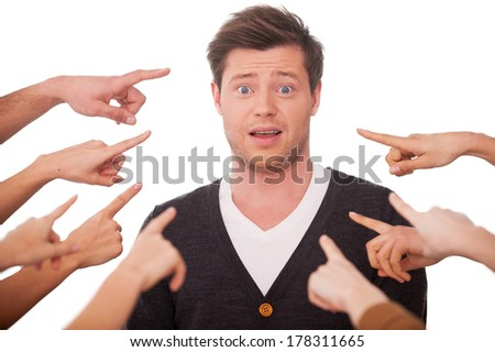 Why me? Shocked young man looking at camera while many hands pointing him  - stock photo