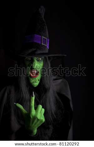 Wicked witch signaling come here, black background. - stock photo
