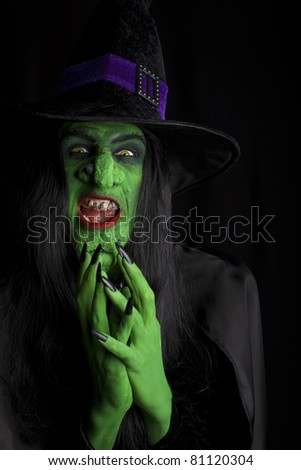 Wicked witch thinking evil thoughts, black background. - stock photo