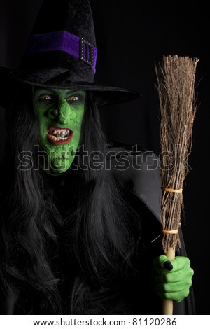 Wicked witch with her broom stick, black background. - stock photo