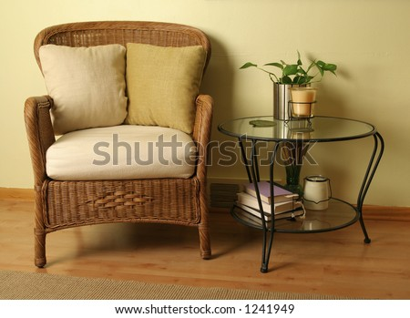 Wicker arm chair and glass table with various items - stock photo