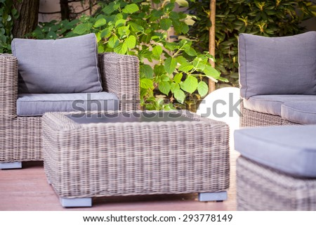 Wicker armchair and table - modern garden furniture - stock photo