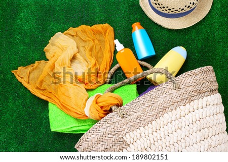 Wicker bag with colorful scarf, towel, bottles of lotions on  green background. - stock photo
