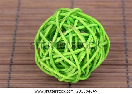 wicker bamboo ball on bamboo mat - stock photo