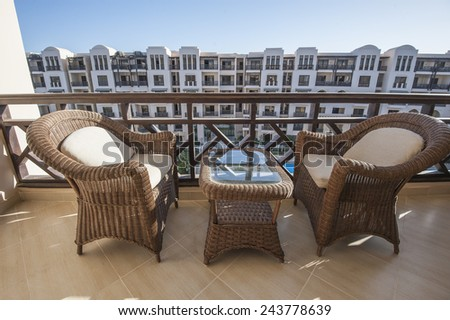 Wicker bamboo chairs and table on tropical apartment balcony - stock photo