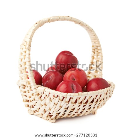 Wicker basked filled with multiple red victoria plums isolated over the white background