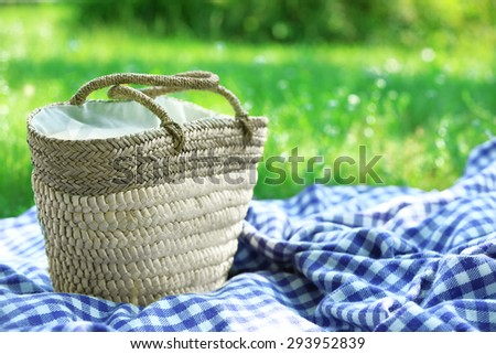 Wicker basket and Plaid for picnic on green grass - stock photo
