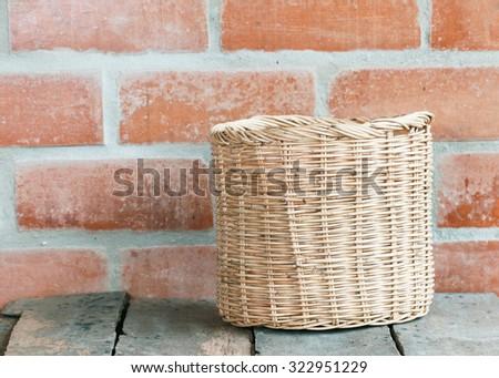 Wicker basket at the brick wall on wooden floor.interior decor. - stock photo