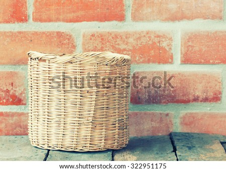 Wicker basket at the brick wall on wooden floor.interior decor -vintage filter effect. - stock photo