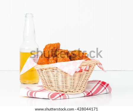 Wicker basket filled with spicy buffalo style chicken wings. - stock photo