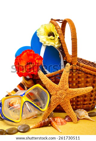 Wicker basket, flip-flops, fishstar, goggles on the towel isolated on white - stock photo