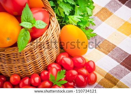 Wicker basket full of fresh tomatoes and cherry tomatoes