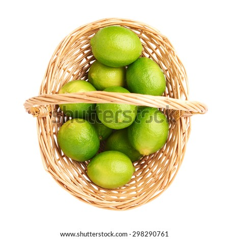 Wicker basket full of multiple ripe limes, composition isolated over the white background, top view - stock photo