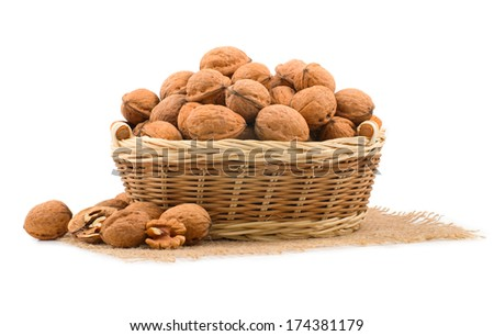 wicker basket full of walnuts on white background