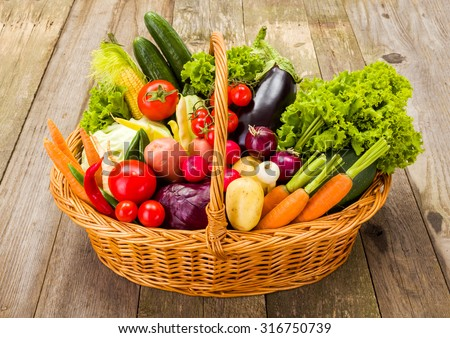 Wicker basket full with various fresh vegetables on rustic wooden background - stock photo