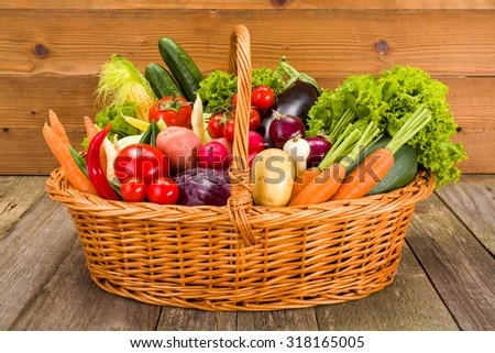 Wicker basket full with various fresh vegetables on rustic wooden background
